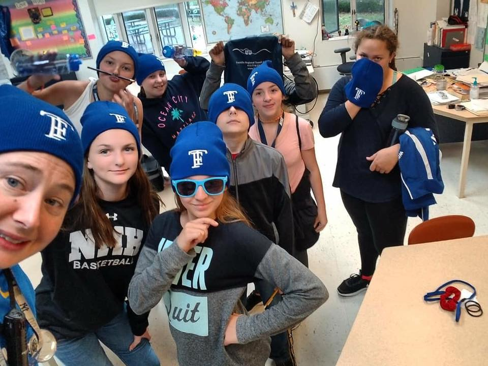 middle school students and teacher wearing blue TF hats
