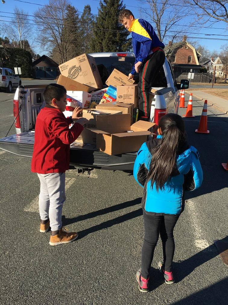 stuents loading food donations onto a pickup truck