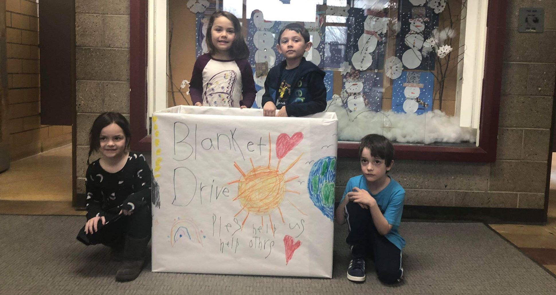 """4 kindergarten students posing with a collection box labeled """"Blanket Drive: Please help us help others"""""""