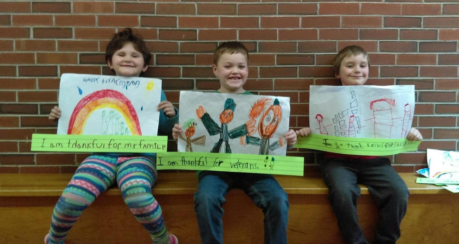 3 first graders holding captioned drawings
