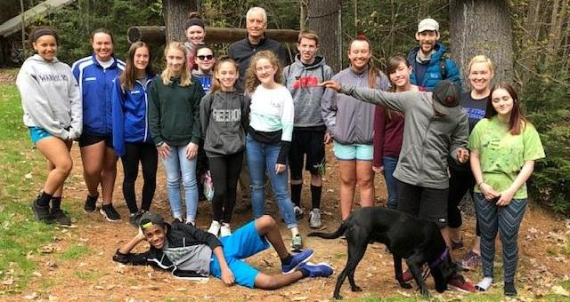 17 students and adults posing for a group photo outdoors in a wooded area in spring